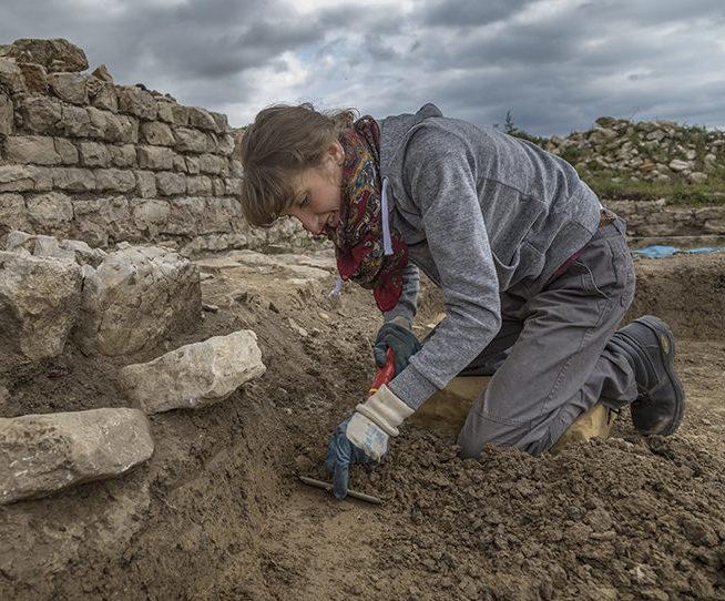 Une archéologue de la SRAAB fouillant la terre avec ses outils sur le site B du Gurtelbach