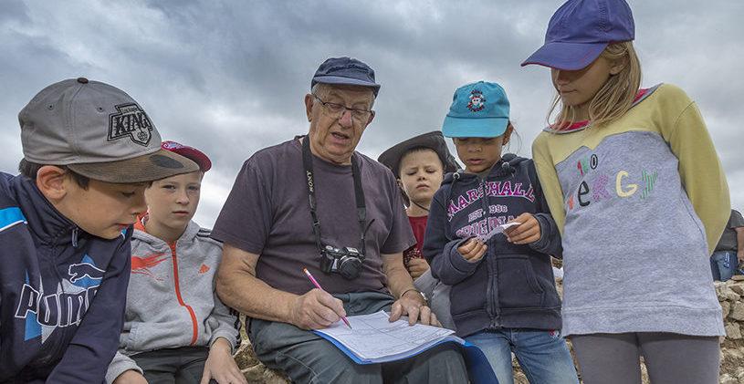 Un bénévole de la SRAAB expliquant le rôle de l'archéologie à des élèves de primaire