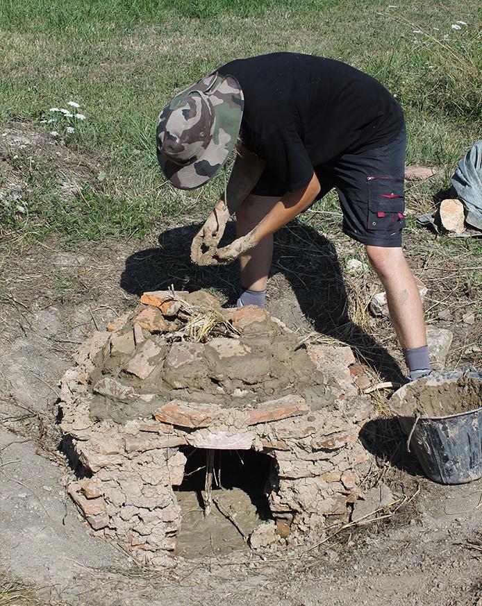 Bénévole de la Société de Recherches Archéologique de l'Alsace Bossue en pleine confection du four à pain antique