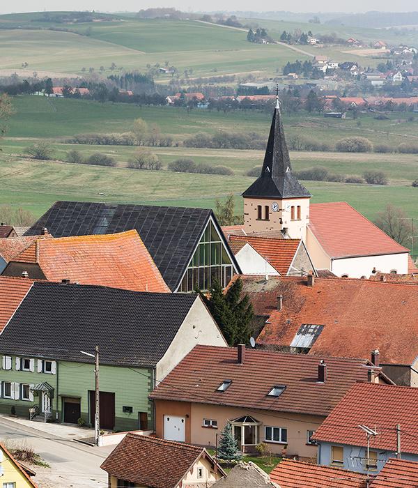 Vue de la façade sud du CIP La Villa, musée d'archéologie, par les hauteurs du village de Dehlingen. Belle carte postale de la campagne d'Alsace Bossue