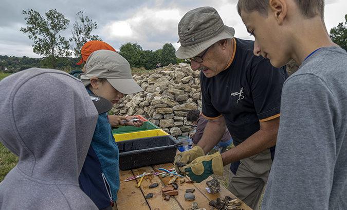 Une archéologue de la SRAAB en compagnie d'écoliers sur le site du Gurtelbach, ils nettoient et font une première analyse des pièces découvertes