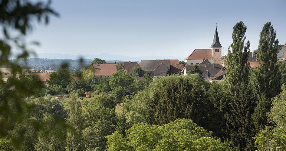 Vue du village de Dehlingen depuis e la façade sud du CIP La Villa, musée d'archéologie, par les hauteurs du village de Dehlingen depuis les sentiers d'interprétation