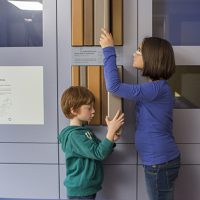Deux enfants qui découvrent des ressources pédagogiques dans la salle bleue de l'exposition du CIP La Villa, musée d'archéologie à Dehlingen