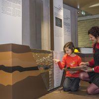 Deux visiteurs, une mère et sa fille, dans le parcours d'exposition du CIP La Villa, musée d'archéologie à Dehlingen. On peut y voir une coupe de terrain permettant de montrer comment les archéologues déterminent l'âge de vestiges anciens
