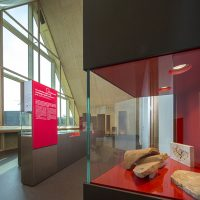 Vue d'un autre angle de l'une des salle d'exposition du CIP La Villa, musée d'archéologie à Dehlingen, présentant des pièces archéologiques retrouvées sur le site du Gurtelbach, au premier plan, des tuiles provenant de la villa